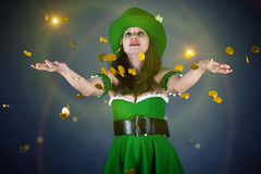 Leprechaun gold coin throws up. A woman dressed as a leprechaun gold coin throws up Stock Images