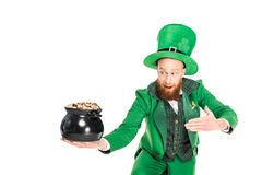 Leprechaun in green suit presenting pot of gold. Isolated on white Royalty Free Stock Images