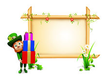 Leprechaun holding gift box with sign Stock Image