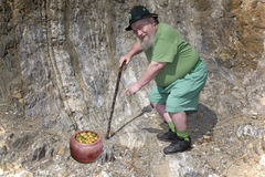 Leprechaun points to his traditional pot of gold Stock Photography