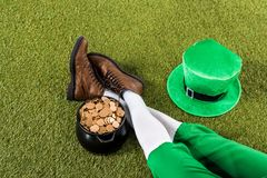 Leprechaun with pot of gold and hat sitting on green grass. Cropped view of leprechaun with pot of gold and hat sitting on green grass Stock Images
