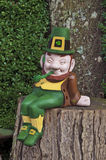 Leprechaun smiling and sitting on tree trunk with pipe Stock Images