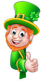 Leprechaun St Patricks Day Cartoon Mascot. Cartoon Leprechaun St Patricks Day character peeking around a sign and giving a thumbs up Stock Images