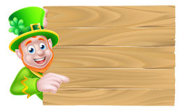 Leprechaun Wooden Sign. Leprechaun cartoon St Patricks Day character peeking around a wooden sign and pointing Royalty Free Stock Photo
