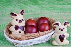 Lepri dei biscotti di Pasqua ed uova colorate in un canestro Fotografie Stock Libere da Diritti