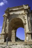 Leptis Magna. Wide angle View of the arch of Septimus Severus at Leptis Magna with man taking picture Royalty Free Stock Photography