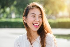Ler den lyckliga unga vuxna asiatiska kvinnan för livsstilen som ler med tänder, utomhus och gå på stadsgatan på solnedgångtid royaltyfri fotografi