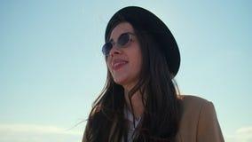 Ler ståenden himmel den unga kvinnan för brunetten i hatt, mot solen och lager videofilmer