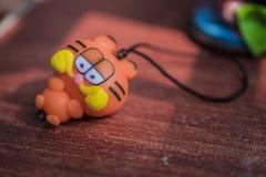 Lera plast- Garfield, liten leksaker, små hantverk som förläggas på morotsfärgade träbräden arkivbilder