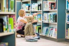 Leraar Assisting Boy In die Boeken binnen selecteren stock afbeeldingen