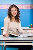 Leraar With Book Sitting bij Bureau in Kleuterschool royalty-vrije stock foto