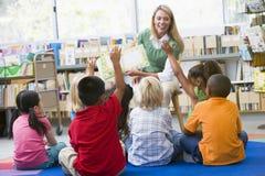 Leraar die aan kinderen in bibliotheek leest