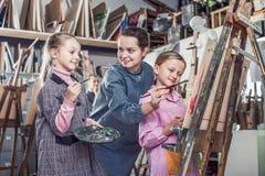 Leraar die bij het schilderen van klasse werken stock afbeeldingen
