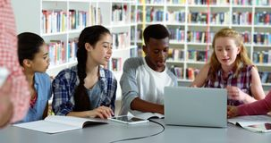 Leraar die digitale tablet gebruiken terwijl student die op achtergrond 4k bestuderen stock video