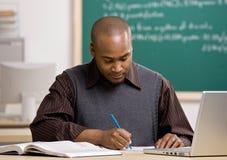 Leraar die documenten in schoolklaslokaal sorteert Stock Fotografie