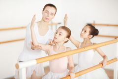 Leraar die doend oefeningen aan meisjes helpen stock foto