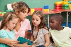 Leraar die een boek lezen aan haar kleuterschoolklasse royalty-vrije stock foto