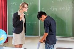 Leraar die een leerling in schoolklasse kritiseren Stock Foto's