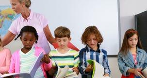 Leraar die jonge geitjes in lezingsboeken helpen in klaslokaal stock videobeelden