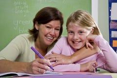 Leraar die jonge student in klaslokaal onderwijst stock afbeeldingen