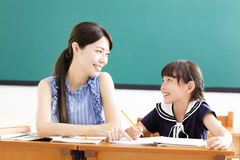 Leraar die kind met het schrijven van les helpen royalty-vrije stock foto