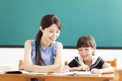 Leraar die kind met het schrijven van les helpen royalty-vrije stock afbeeldingen