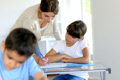 Leraar die kinderen helpen op school stock afbeelding