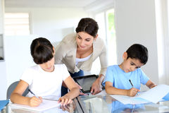 Leraar die kinderen in klaslokaal helpen stock fotografie