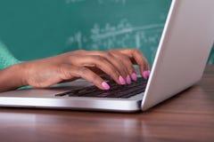 Leraar die laptop met behulp van bij bureau Royalty-vrije Stock Fotografie