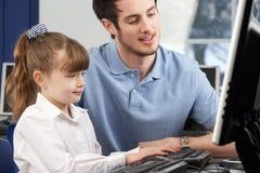 Leraar die meisje helpt dat computer in klasse met behulp van stock foto