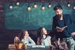 Leraar die met jonge schoolmeisjes bij bureau in klasse werken stock fotografie