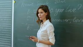Leraar die met klasse dichtbij het bord spreken stock footage