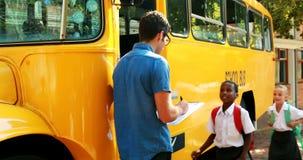 Leraar die opkomst nemen terwijl student die in bus binnengaan stock videobeelden