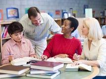 Leraar die rijpe studenten in bibliotheek helpt Stock Foto