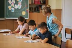 Leraar die schooljonge geitjes helpen die test in klaslokaal schrijven onderwijs, basisschool, het leren en mensenconcept royalty-vrije stock afbeeldingen