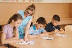 Leraar die schooljonge geitjes helpen die test in klaslokaal schrijven onderwijs, basisschool, het leren en mensenconcept stock foto