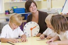 Leraar die schoolkinderen helpt leren om tijd te vertellen Royalty-vrije Stock Afbeelding