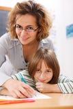 Leraar die schoolmeisje het schrijven bevordert Stock Afbeelding