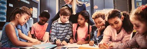 Leraar die schoolmeisje met haar thuiswerk in klaslokaal helpen royalty-vrije stock afbeelding