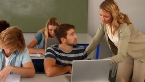 Leraar die student met laptop helpen stock video