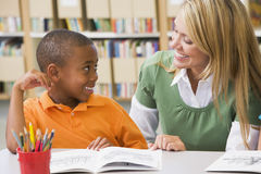 Leraar die student met lezingsvaardigheden helpt Stock Foto's