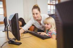 Leraar die student tonen hoe te om een computer te gebruiken stock foto's