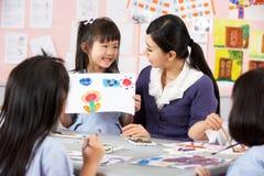 Leraar die Studenten in Chinese School helpt Stock Fotografie