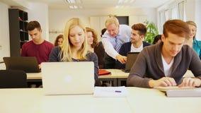 Leraar die studenten in klaslokaal helpt Stock Fotografie