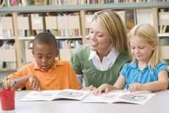 Leraar die studenten met lezingsvaardigheden helpt Stock Fotografie