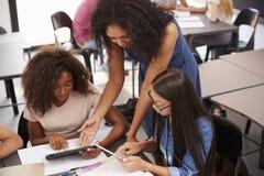 Leraar die studenten met technologie, hoge hoek helpen stock foto's