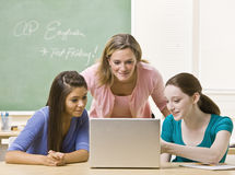 Leraar die studenten op laptop helpt Stock Foto's