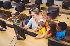 Leraar die studenten tonen hoe te om een computer te gebruiken stock fotografie