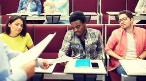 Leraar die tests geven aan studenten bij lezing stock foto