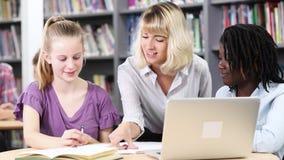 Leraar die twee vrouwelijke middelbare schoolstudenten helpen die bij laptop werken stock footage
